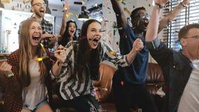emocja Etniczni fan świętują wygranie Confetti 4K zwolnione tempo Namiętna zwolennika krzyka dopatrywania gra na TV zdjęcie stock