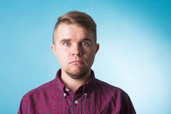 Emocja, reklama i ludzie pojęć, - zdziwiony mężczyzna nad błękitnym tłem zdjęcia stock