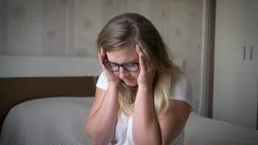 Emocjonalna awaria, zadumana dziewczyna chwytów głowa, i nerwowo siedzimy na łóżku zbiory wideo