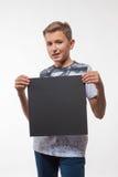 Emocjonalna blond chłopiec w białej koszula z szarym prześcieradłem papier dla notatek Fotografia Stock