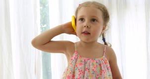 Emocjonalna dziewczyna opowiada na zabawkarskim telefonie zbiory wideo