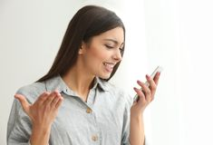 Emocjonalna młoda kobieta opowiada telefonem komórkowym indoors obrazy royalty free