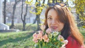 Emocjonalna młoda kobieta z okularów przeciwsłonecznych stać outside z dużym bukietem kolorowi kwiaty podczas wcześnie i ono uśmi zdjęcie wideo