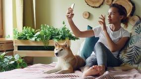 Emocjonalna mieszana biegowa dziewczyna opowiada na telefonie komórkowym robi wideo wywoławczemu ono uśmiecha się i gawędzi patrz zdjęcie wideo