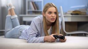 Emocjonalna nastoletnia dziewczyna bawić się wideo grę używać joystick, młodości rozrywka obrazy royalty free