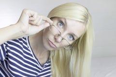 Emocjonalna piękna śliczna blond kobieta jest ubranym szkła, światło - szarość zdjęcie stock