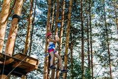 Emocjonalna stara Kaukaska dziewczyna w hełmie rusza się na ciasnych arkanach w arkana parku w lecie pokonywanie zdjęcia royalty free