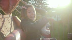Emocjonalna szczęśliwa mała dziewczynka z misiem na carousel przy latem zdjęcie wideo