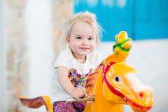 Emocjonalna uśmiechnięta małej dziewczynki jazda na carousel zdjęcia stock