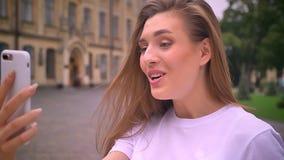 Emocjonalna wspaniała caucasian kobieta ma wideo wzywał ulicę, śmiający się i opowiadający w jej smartphone, dzień