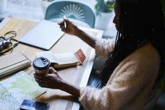 Emocjonalnej pięknej afro amerykańskiej kobiety smakowita kawa i używać nowożytną technologię Zdjęcia Stock