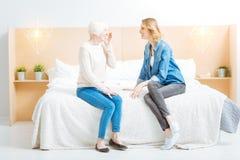 Emocjonalni życzliwi krewni śmia się podczas gdy siedzący na dużym miękkim łóżku wpólnie obraz stock