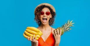 Emocjonalni czarni dziewczyny mienia banany i ananas obrazy royalty free