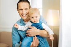Emocjonalni potomstwa ojcują czuciowy szczęśliwego podczas gdy uśmiechający się jego uroczego dziecka i ściskający Obraz Royalty Free
