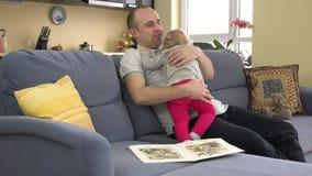 Emocjonalnie czyta książkę z ojcem na kanapa pokoju mała dziewczynka 4K zbiory wideo