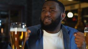 Emocjonalny amerykanin afrykańskiego pochodzenia mężczyzna głośno skanduje siedzieć w sporta barze, poparcie zbiory