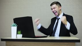 Emocjonalny biznesmen świętuje wygrywający transakcję, dźwiganie, krzyczący z radością i gestykulujący z jego rękami zdjęcie wideo