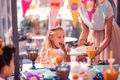 Emocjonalny dziewczyny czuć excited podczas gdy patrzejący jej urodzinowego tort zdjęcia royalty free