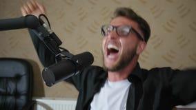 Emocjonalny facet Macha ręki w eyeglasses i rozprasza papier indoors zdjęcie wideo