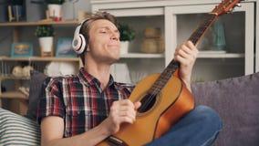 Emocjonalny facet wtedy śmia się jest śpiewający gitarę i bawić się podczas gdy słuchający muzyka w hełmofonach mieć zabawę ładny zbiory wideo