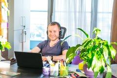 Emocjonalny mężczyzna patrzeje ekran komputerowego i uczestniczy w onlinym spotkaniu w hełmofonach, gesty, konferencja z biznesow fotografia stock