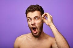 Emocjonalny mężczyzna skuba jego brwi z pincetami zdjęcia stock