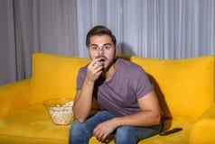 Emocjonalny mężczyzny dopatrywanie z popkornem TV na leżance fotografia royalty free