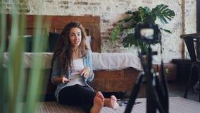 Emocjonalny młodej kobiety vlogger jest opowiadający magnetofonowego wideo z fachową kamerą dla interneta blogu i gestykulujący d zdjęcie wideo