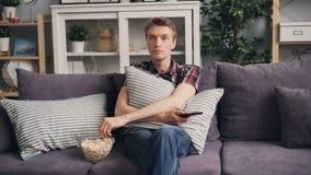 Emocjonalny młody człowiek ogląda horror na TV w domu, je popkorn i chuje za poduszki obsiadaniem na leżance, zbiory wideo