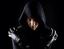 Emocjonalny, młody i atrakcyjny zabójca w rękawiczkach na czarnym tle, obraz stock