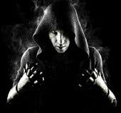 Emocjonalny, młody i atrakcyjny zabójca w rękawiczkach na czarnym tle, fotografia stock