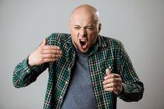 Emocjonalny młody przystojny mężczyzna krzyczy nad beżowym tłem Zdjęcie Royalty Free