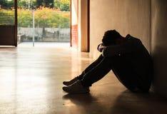 Emocjonalny moment: mężczyzna mienia głowy siedząca depresja na kolanach, zaakcentowana smutna młoda samiec ma umysłowych problem zdjęcie stock