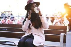 Emocjonalny piękny afro amerykański kobiety obsiadanie na ławce outdoors Zdjęcia Royalty Free