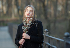 Emocjonalny portret młoda szczęśliwa piękna kobieta jest ubranym czarnego żakiet pozuje na moscie przy evening g z bukietem wierz zdjęcie stock