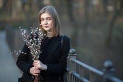 Emocjonalny portret młoda szczęśliwa piękna kobieta jest ubranym czarnego żakiet pozuje na moscie przy evening g z bukietem wierz obraz stock