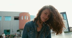 Emocjonalny portret urocza uśmiechnięta dziewczyna aktywnie trząść jej ciemnego kędzierzawego włosy plenerowego z brasami na jej  zbiory