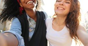 Emocjonalny selfie radośni ono uśmiecha się wielokulturowi girlfrineds robi śmiesznym twarzom podczas gdy chodzący wzdłuż ulicy zbiory wideo