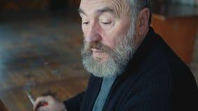 Emocjonalny zmęczony starego człowieka obsiadanie, dymienia papierosowy główkowanie, chrobotliwy ucho 4K zbiory