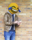 Emoji ballhead man laughing. Emoji ballhead man looking to his smarphone and laughing stock images