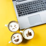 Emoji for communication in social networks. Smile emoji painted on cups of cappuccino next to the laptop on a yellow background. Emotions and communication stock photo