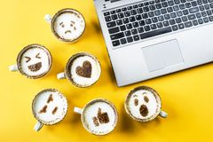 Emoji for communication in social networks. Smile emoji painted on cups of cappuccino next to the laptop on a yellow background. Emotions and communication royalty free stock photos
