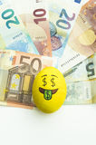 Emoji Easter egg with facial expression. `I love money` placed on euro paper money royalty free stock photography