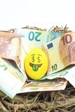 Emoji Easter egg with facial expression `I love money` placed on euro paper money.  stock images