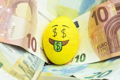 Emoji Easter egg with facial expression `I love money` placed on euro paper money.  royalty free stock image