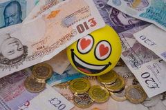 Emoji feliz sonriente cubierto en dinero británico imagen de archivo