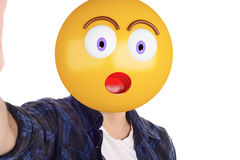 Emoji head man taking selfie. Portrait of an emoji head man taking selfie. Isolated white background royalty free stock photo