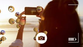 Emoji icons with a woman using smartphone in the background stock footage