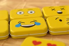 Emoji Metal Tins. Some emoji metal tins or smiley boxes, on a brown background stock photos
