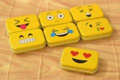 Emoji Metal Tins. Some emoji metal tins or smiley boxes, on a brown background royalty free stock images